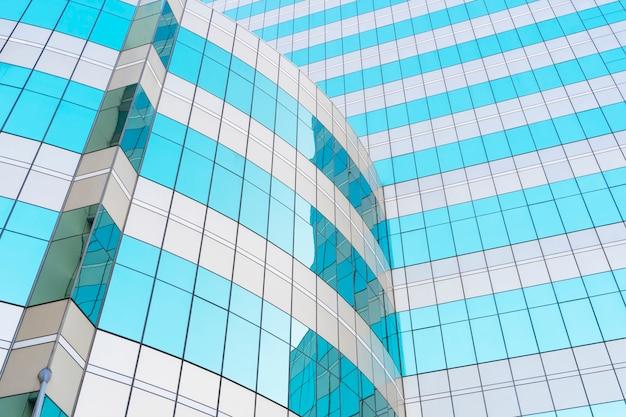 Abstrakter hintergrund vom blauen glasfenster im modernen gebäude mit himmel- und wolkenreflexion.
