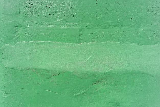 Abstrakter hintergrund vom grün gemalt auf betonmauer mit verkratzt.