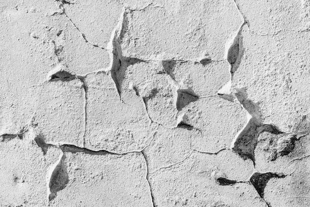 Abstrakter hintergrund von der weißen betonwand mit geschältem und gerissenem.