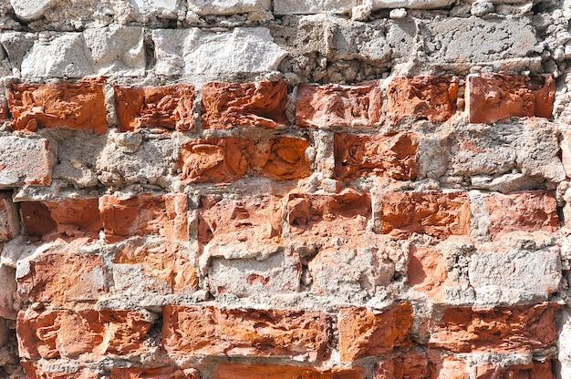 Abstrakter hintergrund von einem schädigenden ziegelstein und von einer maurerarbeit