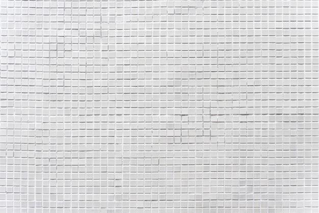 Abstrakter hintergrund von verzierten grauen ziegelsteinmosaikfliesen auf wand.