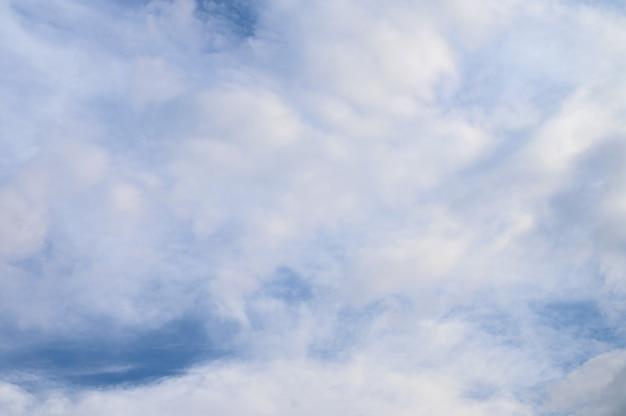 Abstrakter hintergrund von weißen flauschigen wolken auf einem strahlend blauen himmel.