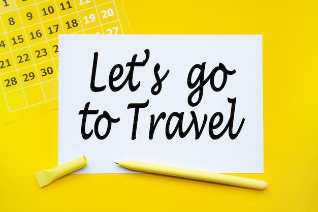 Abstrakter kalender, papier, kugelschreiber auf gelbem hintergrund mit text lassen sie sich auf reisen gehen.