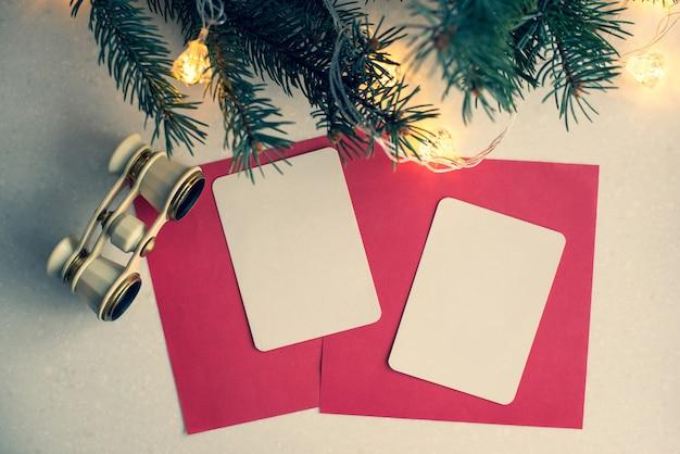 Abstrakter kreativer weihnachtshintergrund mit operngläsern, tannenzweig, weißbuch für ihren text. vorlage.