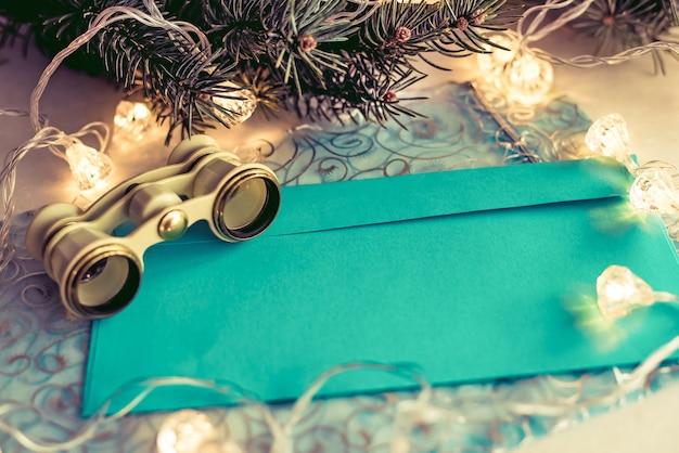 Abstrakter kreativer weihnachtshintergrund mit operngläsern, tannenzweig, weißbuch für ihren text