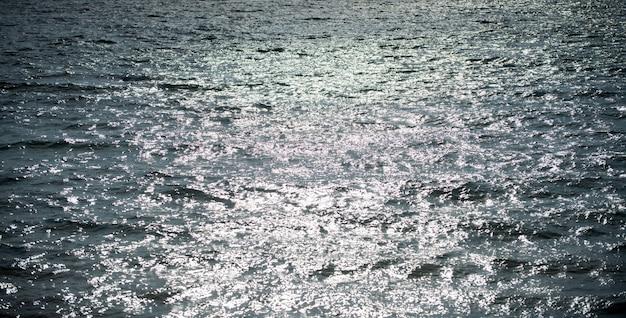 Abstrakter meeresnaturhintergrund. wasserwellen im sonnenlicht mit kopienraum. tropischer strand. wasserstelle. aqua meerwasseroberfläche.