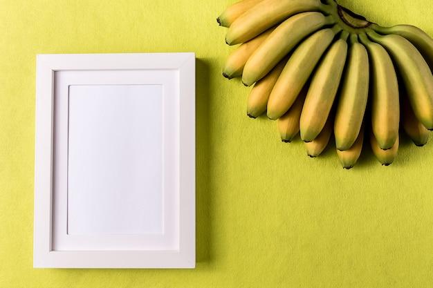 Abstrakter minimalismus colofrul papierhintergrund mit leerem bilderrahmen und banane