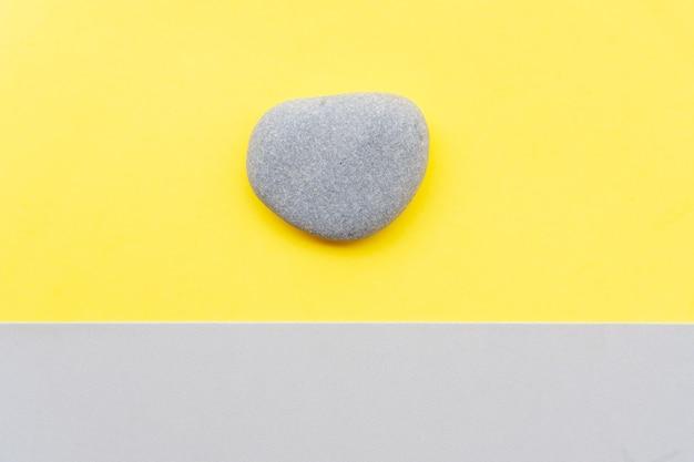 Abstrakter moderner handgemachter papierhintergrund mit einem stein in ultimativem grau und leuchtenden gelben farben