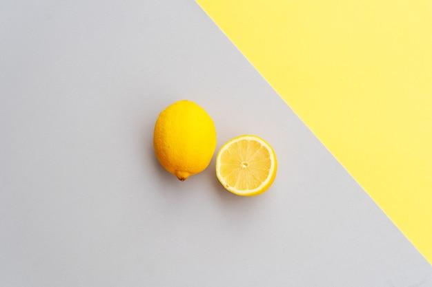 Abstrakter moderner handgemachter papierhintergrund mit zitronenfrüchten in ultimativen grauen und leuchtenden gelben farben