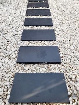 Abstrakter polierter plattenweg aus stein auf schotterhintergrund