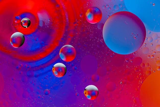 Abstrakter raumhintergrund von öltropfen auf der wasseroberfläche in neonfarbe