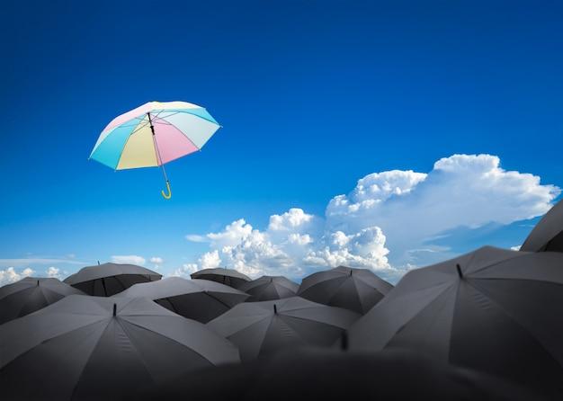 Abstrakter regenschirm, der über viele schwarze regenschirme fliegt