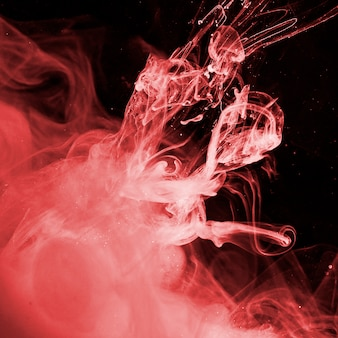 Abstrakter roter dunst in der dunklen flüssigkeit
