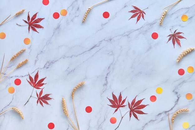 Abstrakter saisonaler hintergrund des herbstes mit natürlichen weizenohren, herbstahornblättern und papierkreiskonfetti.