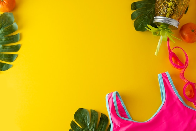 Abstrakter sommerhintergrund. rosa badeanzug und ananasglas für saft.