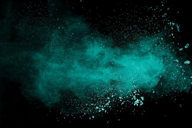 Abstrakter spritzer von grün gefärbtem pulver auf schwarzem hintergrund. explosion des grünen pulvers.