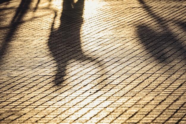 Abstrakter städtischer hintergrund mit dem diffusen schatten des mannes gehend bei sonnenuntergang, einsamkeitskonzept.