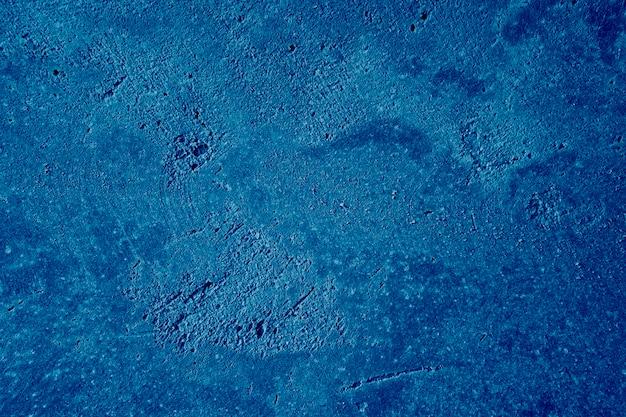 Abstrakter tiefblauer hintergrund. detaillierte putztexturwand in blau gefärbt. bemalte wand.