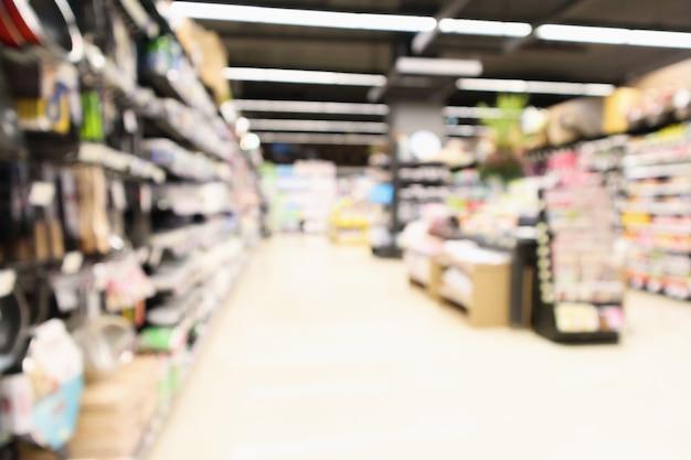 Abstrakter unschärfe-supermarkt mit antihaft-pfanne auf den regalen der küchenutensilien im lebensmittelgeschäft defokussierten hintergrund