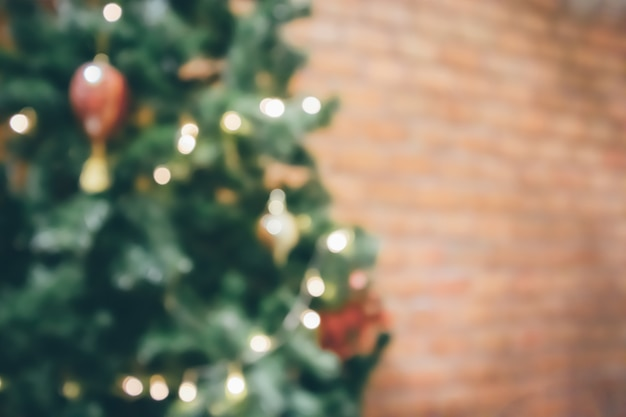 Abstrakter unschärfe verzierter weihnachtsbaum mit flitter-neujahrsfeiertagshintergrund