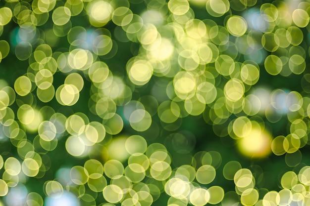 Abstrakter unschärfedekorationsball und helle schnur auf weihnachtsbaum mit bokeh beleuchten