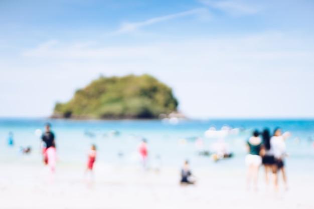 Abstrakter unschärfehintergrund des strandes und der leute, die tropischen strand genießen.