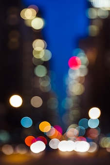 Abstrakter unscharfer stadthintergrund. straßenlaternen der großstadt bei nacht. lichter und schatten von new york city