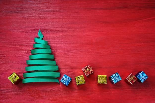 Abstrakter weihnachtsbaum mit kleinen geschenken herum auf der roten oberfläche.