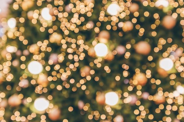 Abstrakter weihnachtsfeiertag mit festlichem goldbokeh-licht auf baum unscharfem hintergrund