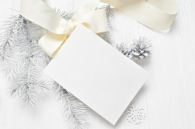 Abstrakter weihnachtshintergrund, weißes blatt papier liegend unter kleinen dekorationen