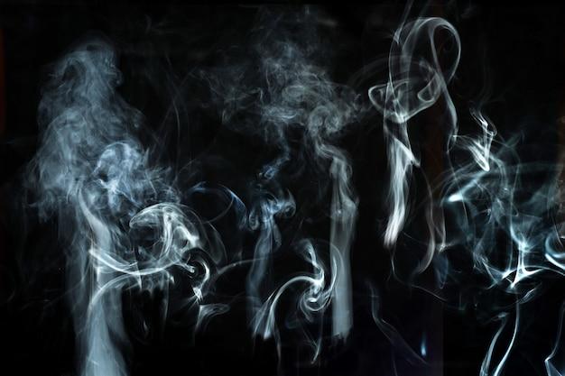 Abstrakter weißer raucheffekt lokalisiert auf schwarzem hintergrund.