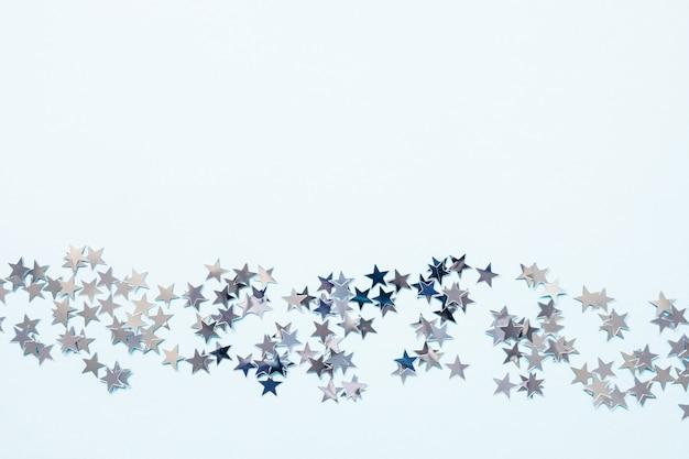 Abstrakter winterhintergrund mit konfetti-sternen der silberfolie auf blau