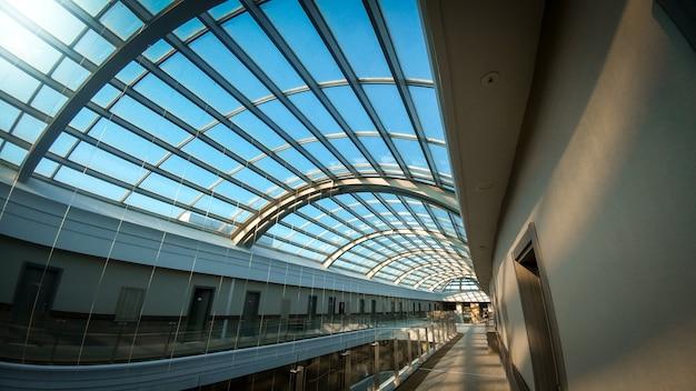 Abstraktes architekturbild des langen korridors und der glasdachkuppel im modernen gebäude