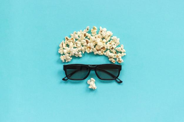 Abstraktes bild des betrachters, der gläser 3d und des popcorns auf blauem hintergrund.