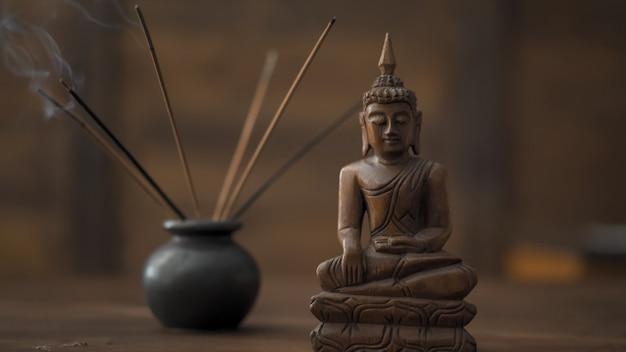 Abstraktes bild eines modernen büros im orientalischen stil, selektiver fokus auf räucherstäbchen und hölzerne buddha-figur am tisch