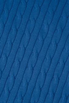 Abstraktes blaues strickmuster, hintergrund. garn strukturierter, gewebter stoff. verzierung der zöpfe des pullovers. stofftapete.