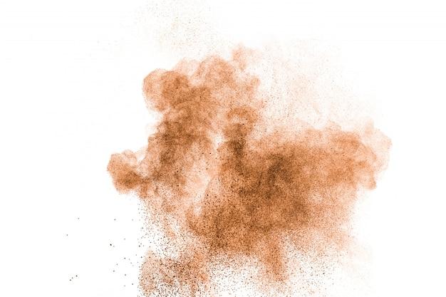 Abstraktes braunes pulver bespritzt auf weißem hintergrund. abstraktes design der farbstaubwolke gegen weiße wand.