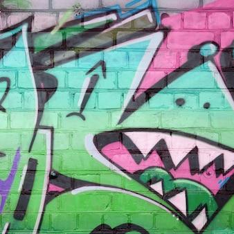 Abstraktes buntes fragment von graffiti-gemälden auf alter backsteinmauer in grünen farben