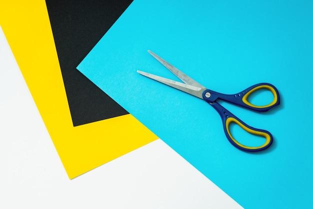 Abstraktes farbpapier und bunte papieroberfläche mit schere oben.