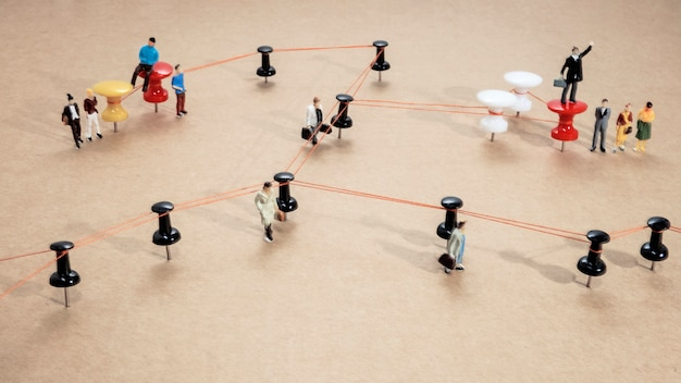 Abstraktes foto der büroarbeit. verdrahtete punkte auf holzoberfläche mit kleinen mannfiguren.
