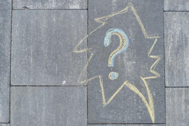 Abstraktes fragezeichen gezeichnet in buntstiften auf grauem asphalt