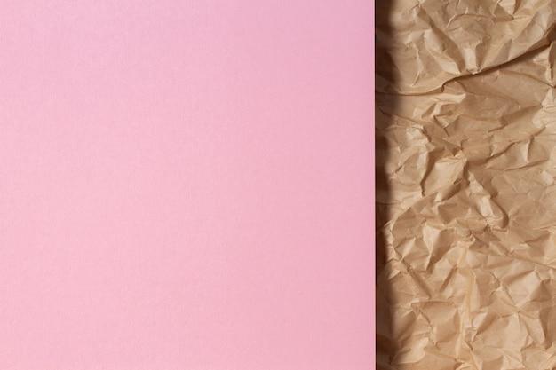 Abstraktes geometrisches papierbeschaffenheitshintergrund leeres hellrosa farbpapierblatt über recyceltem zerknittertem braunem papierhintergrund
