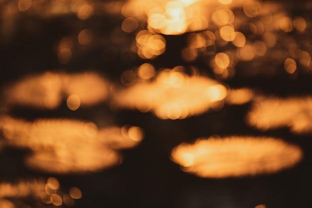 Abstraktes goldbokeh mit sonnenuntergang auf schwarzem hintergrund.