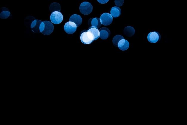 Abstraktes hintergrund blaues bokeh mit schwarzem hintergrund.