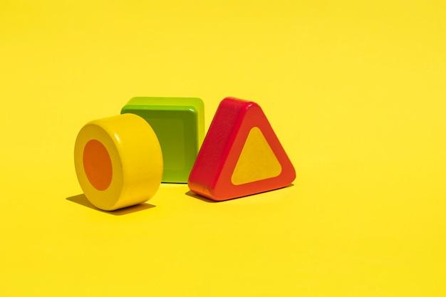 Abstraktes konzept mit holzklötzen auf einem gelben klaren.