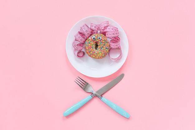 Abstraktes lustiges gesicht der frau vom donut mit den augen und dem haar vom zentimeterband auf platte. diät oder ungesundes nahrungsmittelkonzept