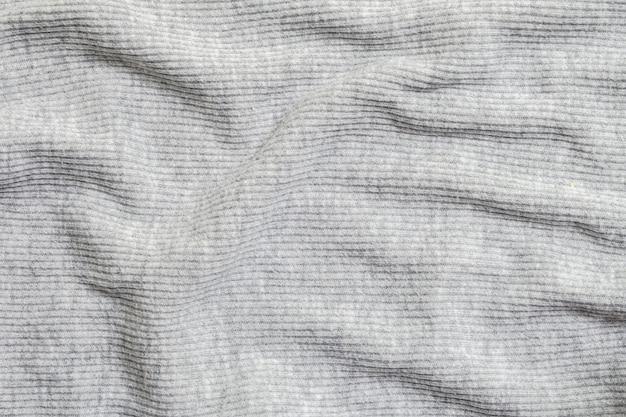 Abstraktes muster der nahaufnahme am faltigen grauen frauenkleidungs-strukturierten hintergrund