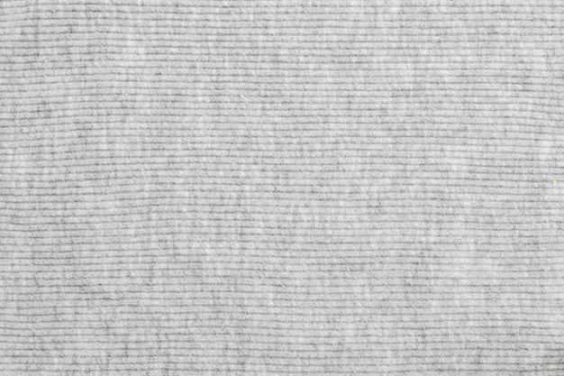 Abstraktes muster der nahaufnahme am strukturierten hintergrund der grauen frauenkleidung