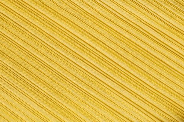 Abstraktes muster der nahaufnahme am strukturierten hintergrund der kleidung der gelben frauen