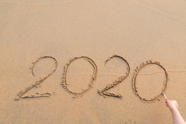 Abstraktes nachrichtenjahr 2020 geschrieben auf strandsandhintergrund
